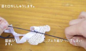 かぎ針編みでクマのマスコットを作っています。最後にゴムを結びつけてヘアゴムに仕立てている様子。