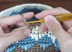 エコアンダリヤを使ってかぎ針編みで模様編みを編んでいます。糸を引き出したら左の親指を使って糸を押さえながら細編みを仕上げましょう。
