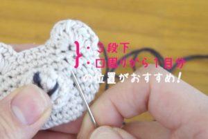 かぎ針を使ってクマのマスコットを編んでいます。顔のパーツを刺繍で縫い付けています。