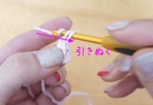 かぎ針編みで伸縮する作り目を編んでいます。かぎ針にかかっている糸を全部引き抜きます。