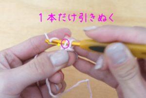 かぎ針編みで伸縮する作り目を編んでいます。1本だけ糸をかぎ針から引き抜きます。