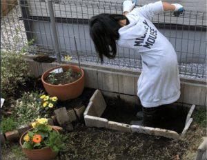 自宅の庭に手作りの砂場を作るために穴を掘る画像